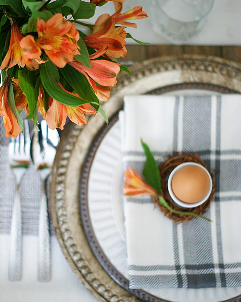 Over head view of Spring place setting with white and bronze plate and charger.