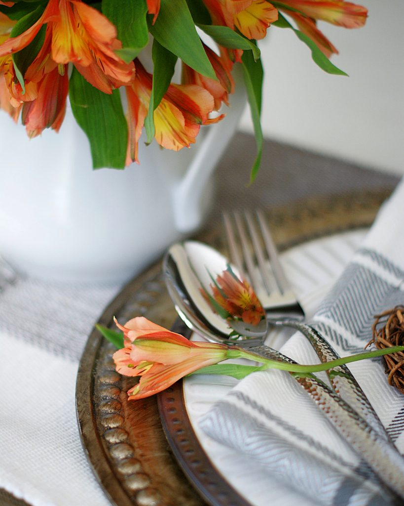 Utensils and one flower on the decorative edges of the charger and white and bronze plate