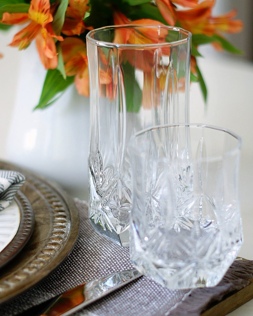 Two crystal glasses with orange/peach flowers in the background