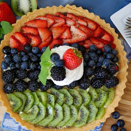 A completed fruit tart garnished with whipped topping and more fruit.