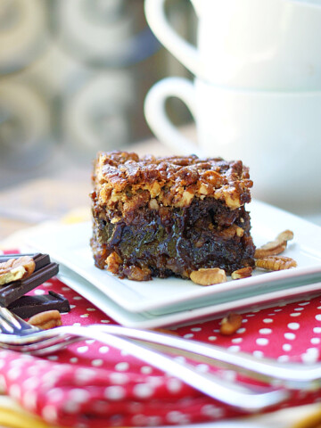 A gooey pecan pie brownie on a white place with coffee cups in the background