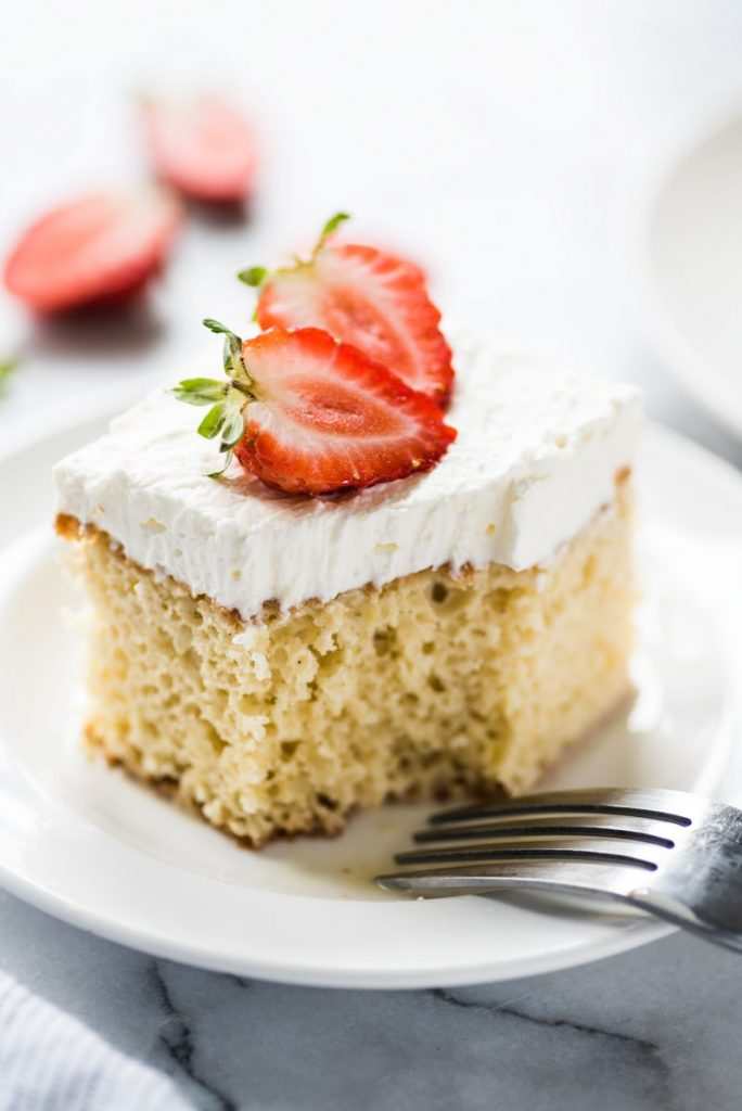 A slice of tres leches cake topped with strawberries for cinco de mayo.