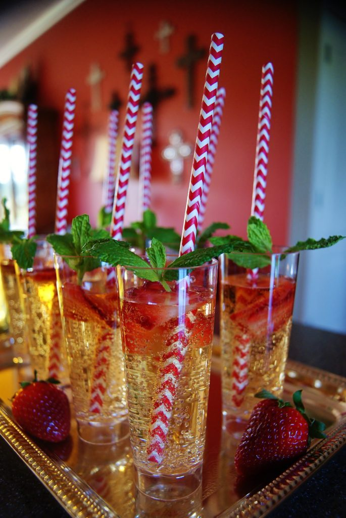 Tall tumblers filled with bubbly champagne julep punch, garnished with strawberries.
