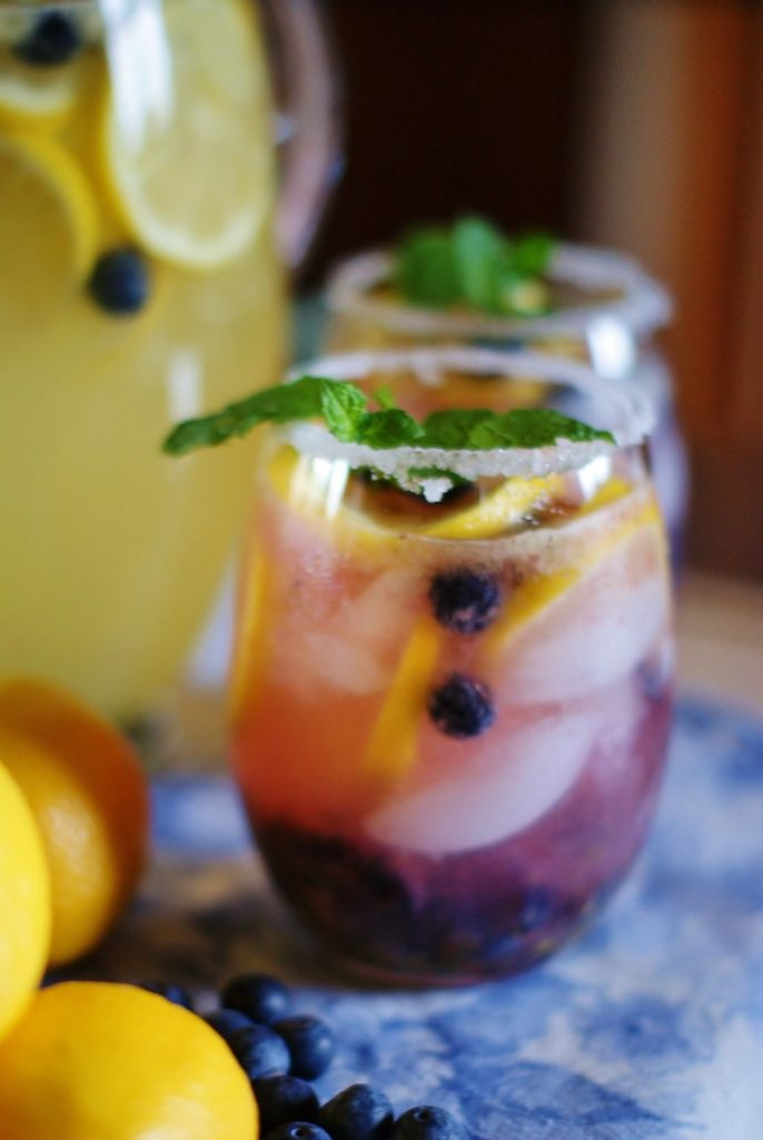Sugared glasses filled with lavender colored lemonade, garnished with blueberries and lemon slices.