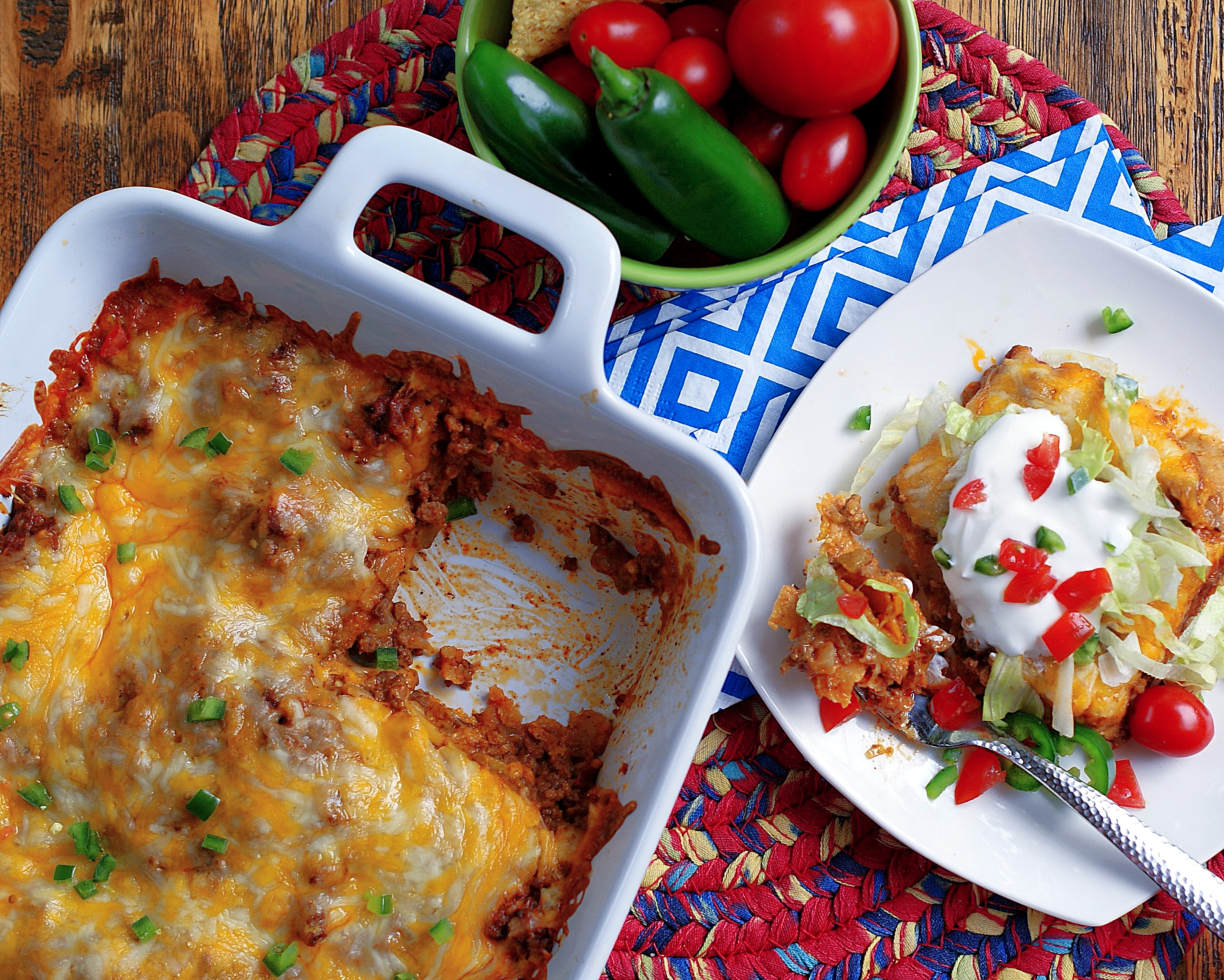 An aerial view of a dish of layered beef enchiladas and a slice of the beef enchiladas on a plate.
