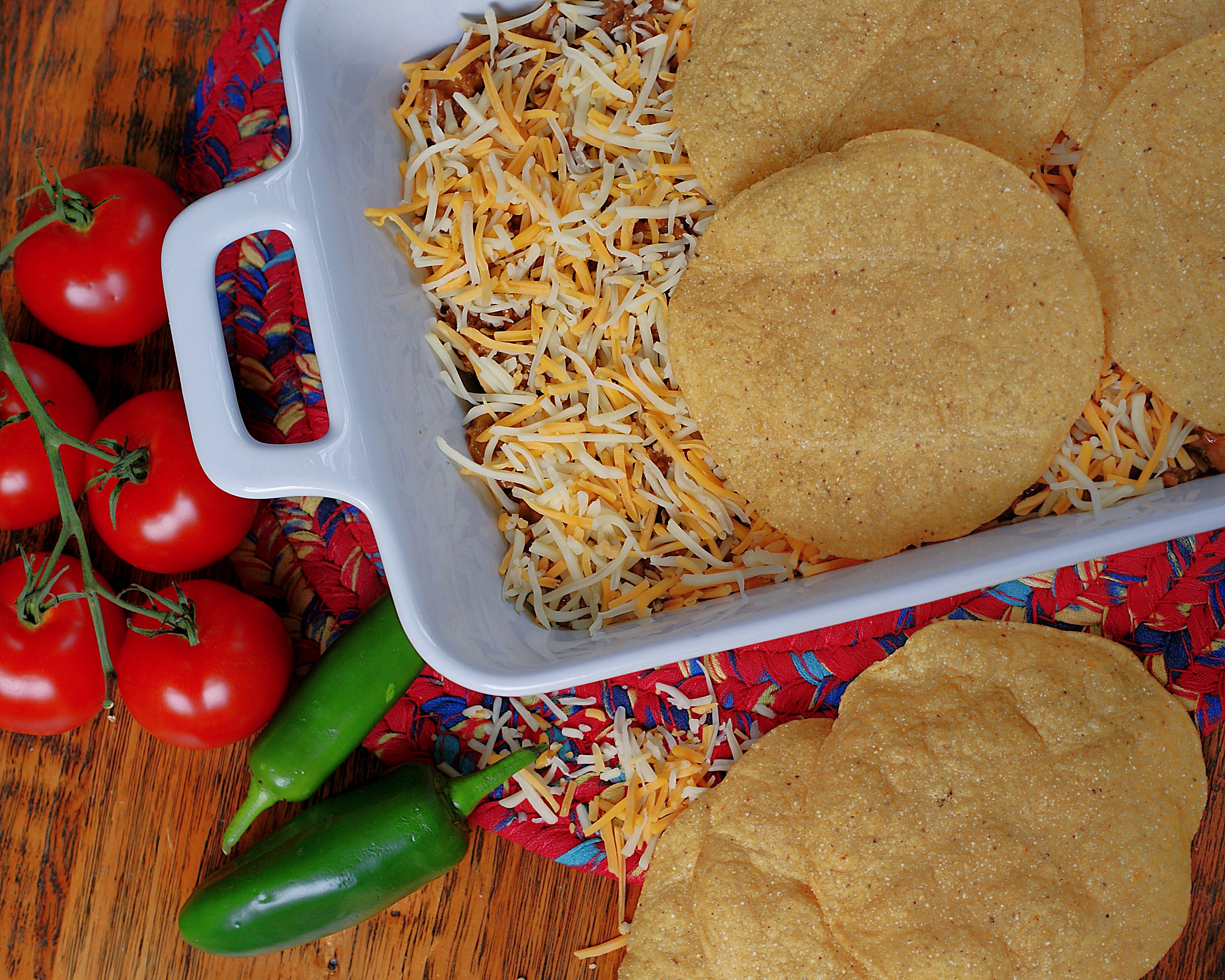Layering beef, cheese and tostadas in a casserole dish.