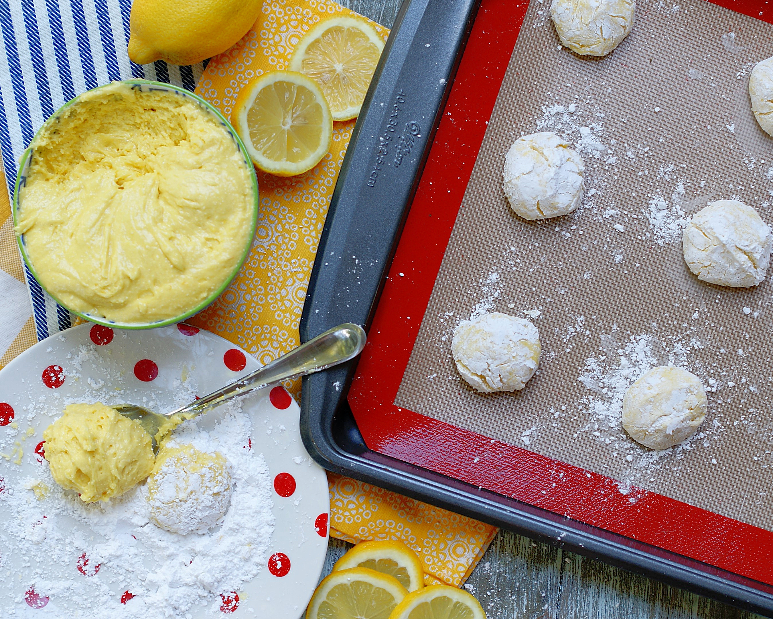 Lemon cookie dough, powdered sugar and rolled cookie balls ready to be baked.