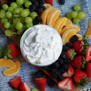 An overhead of a full bowl of marshmallow fruit dip with lots of fruit all around.