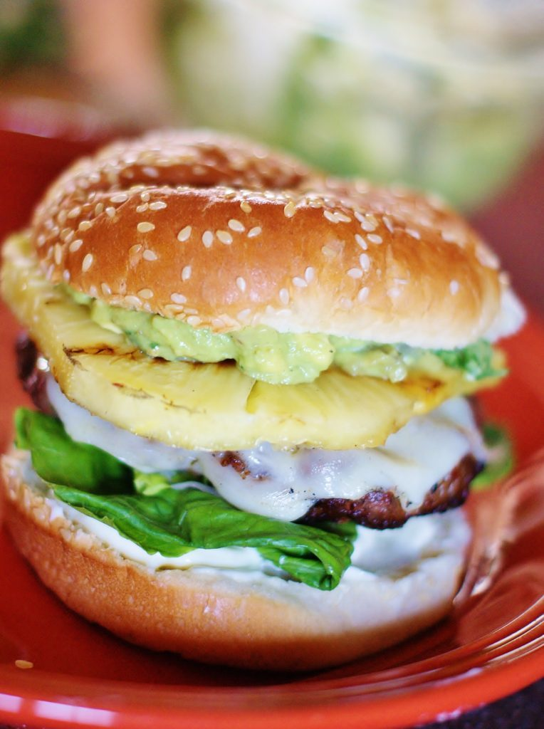 A Grilled Pineapple Burger with melted cheese and sesame seed bun.