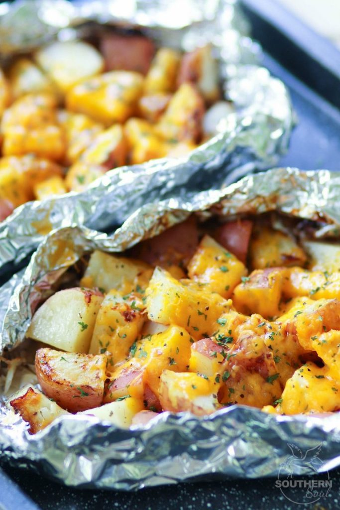 Red potatoes with melted cheese and Ranch seasoning in a foil packet cooked on a grill.