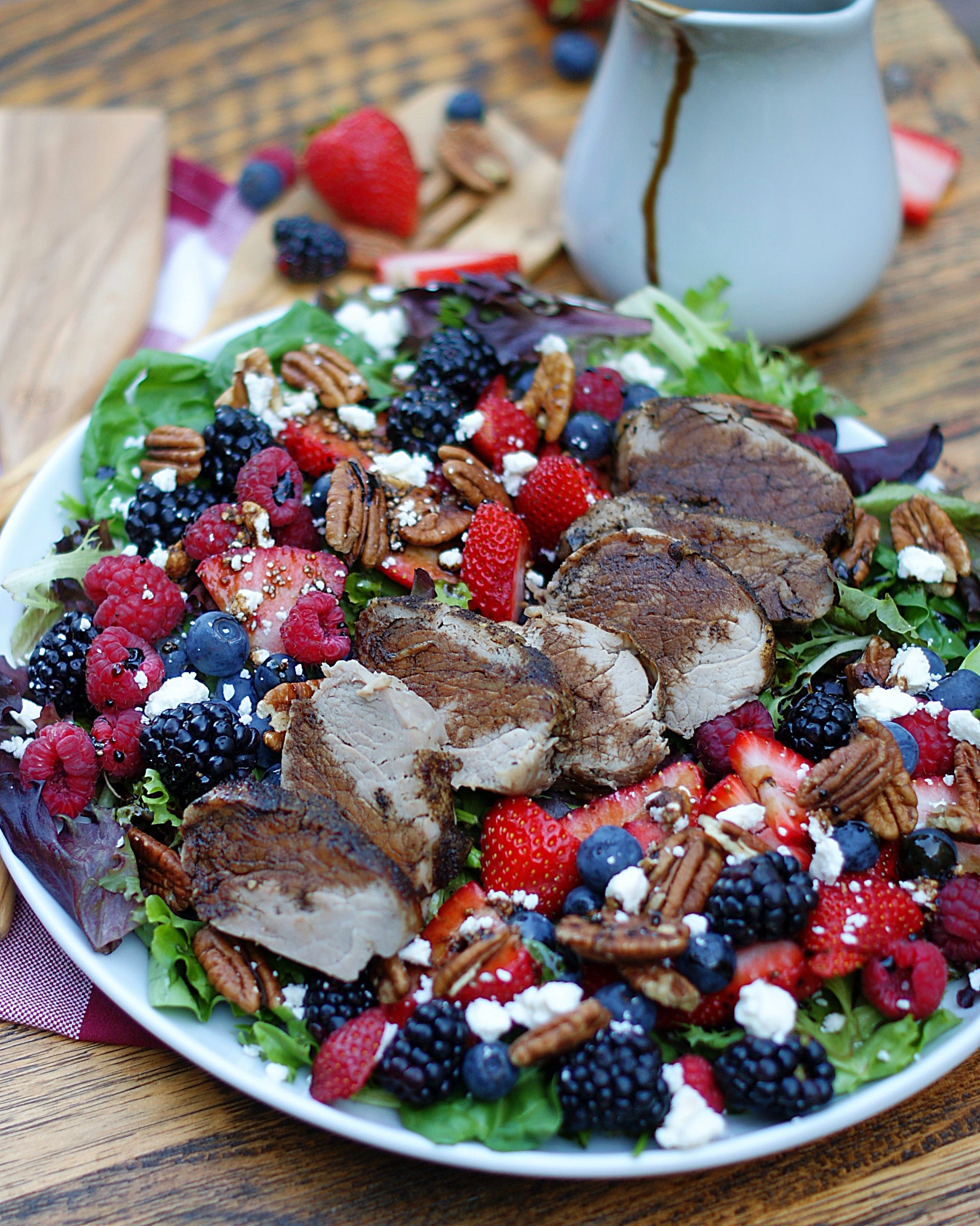 Berry Salad with balsamic dressing drizzled all around and peppered pork tenderloin.