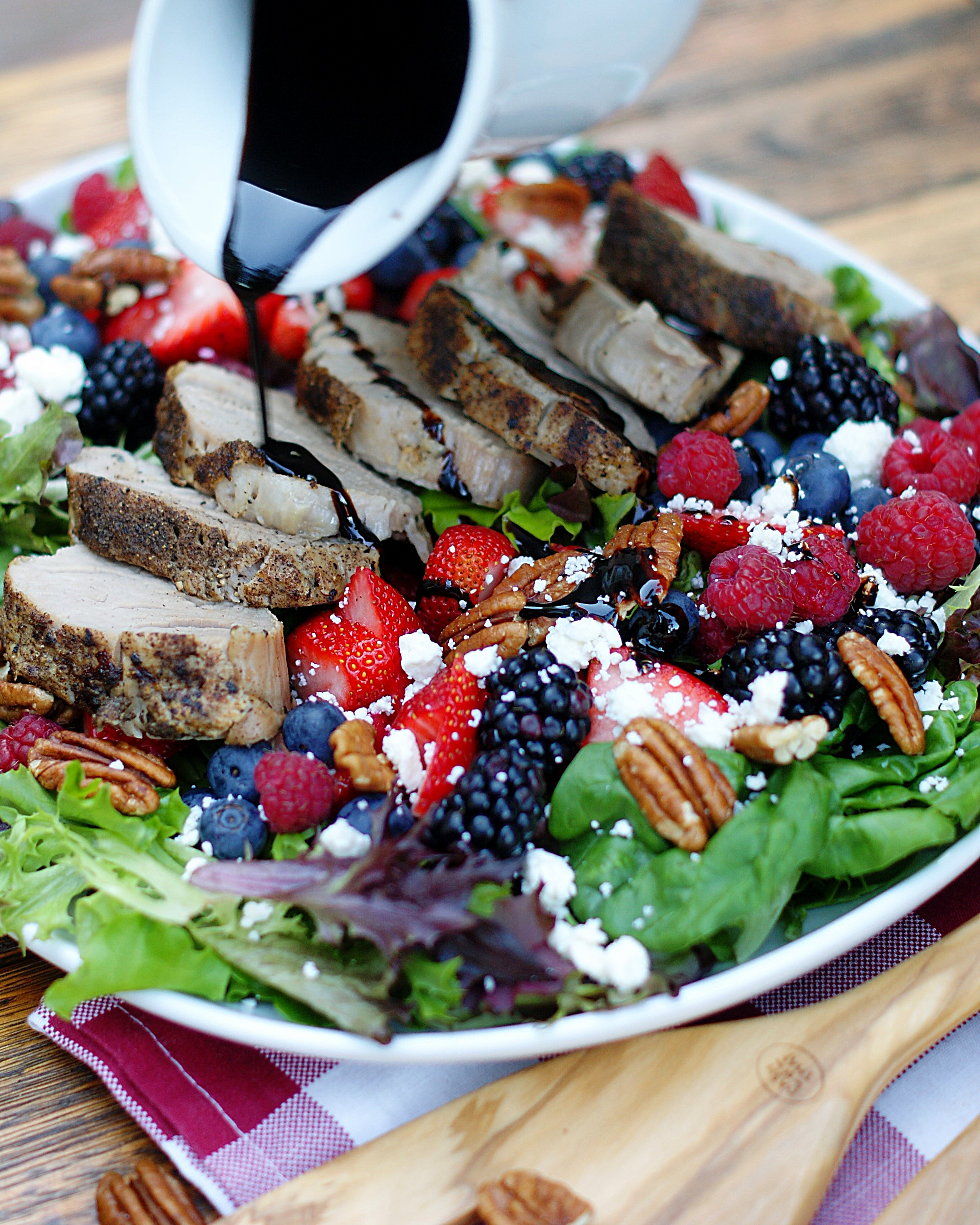Pouring the cherry balsamic dressing on the berry salad with pork tenderloin.