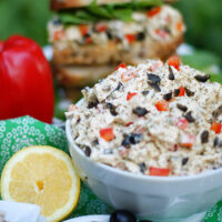 A bowl of lemon chicken salad with a chicken salad sandwich in the background.