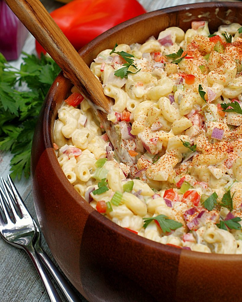 A creamy macaroni salad filled with pickles, red bell pepper, onion and celery