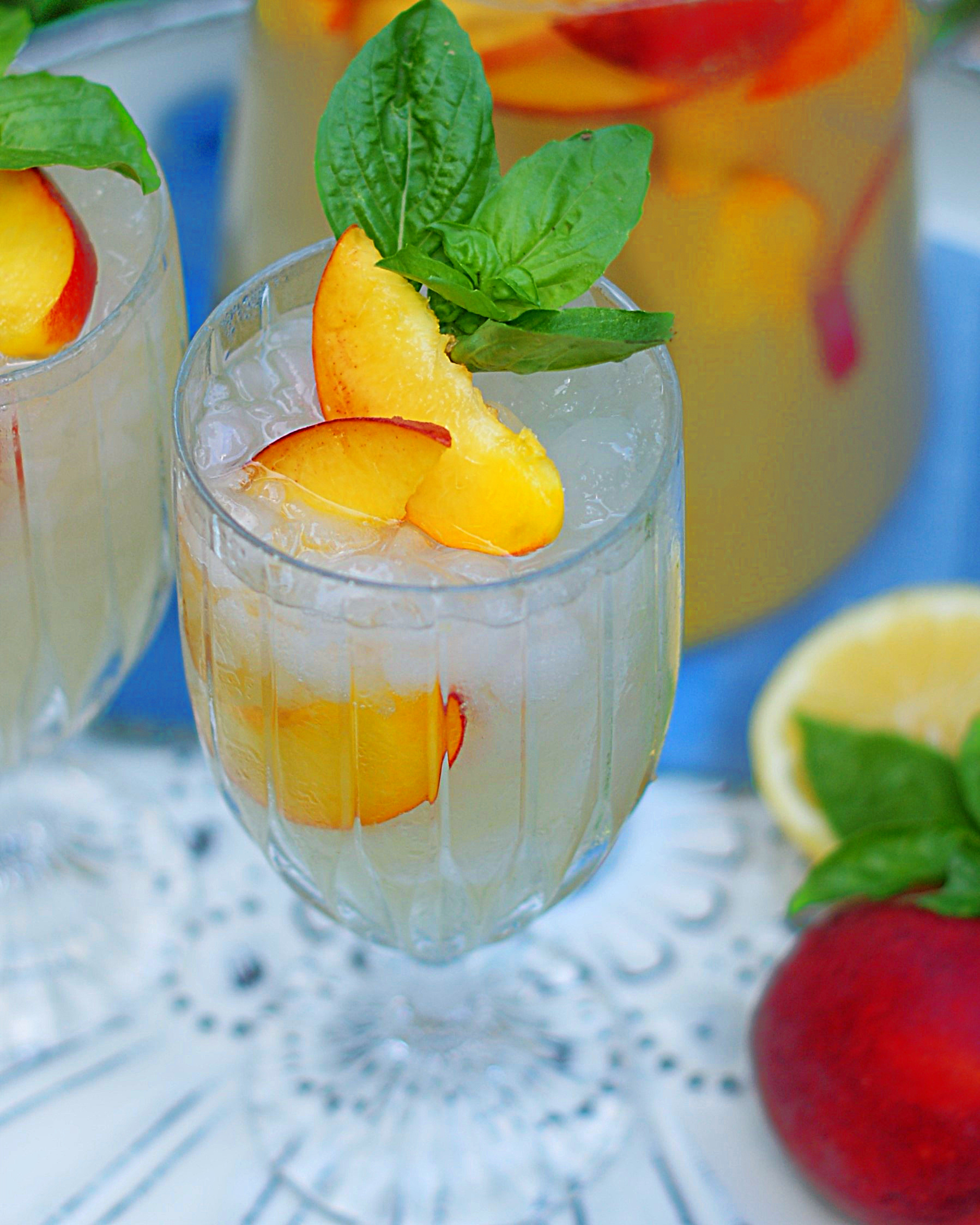 A crystal glass filled with sparkling peach lemonade, garnished with peach slices and basil.