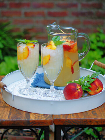 A pitcher and 2 glasses of peach lemonade on a white serving tray on a table in a garden.