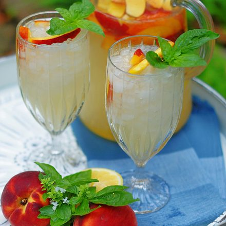 2 glasses of sparkling peach lemonade with peaches and basil as garnish.