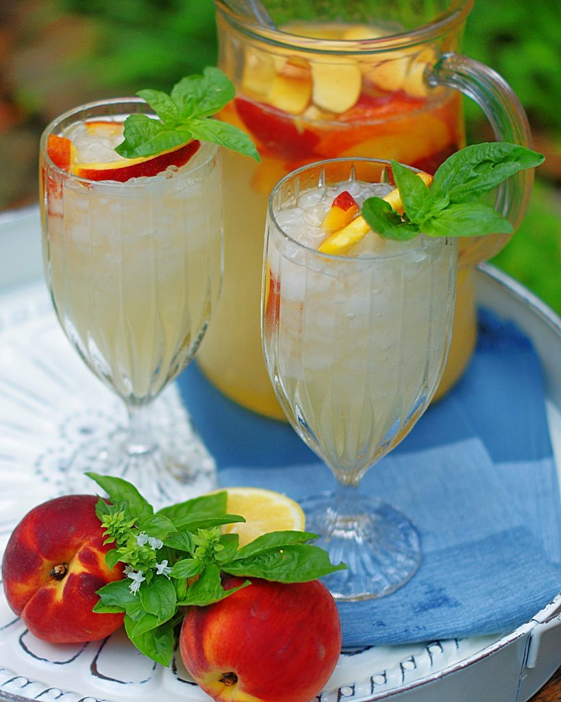 2 glasses of peach lemonade garnished with peach slices and basil.