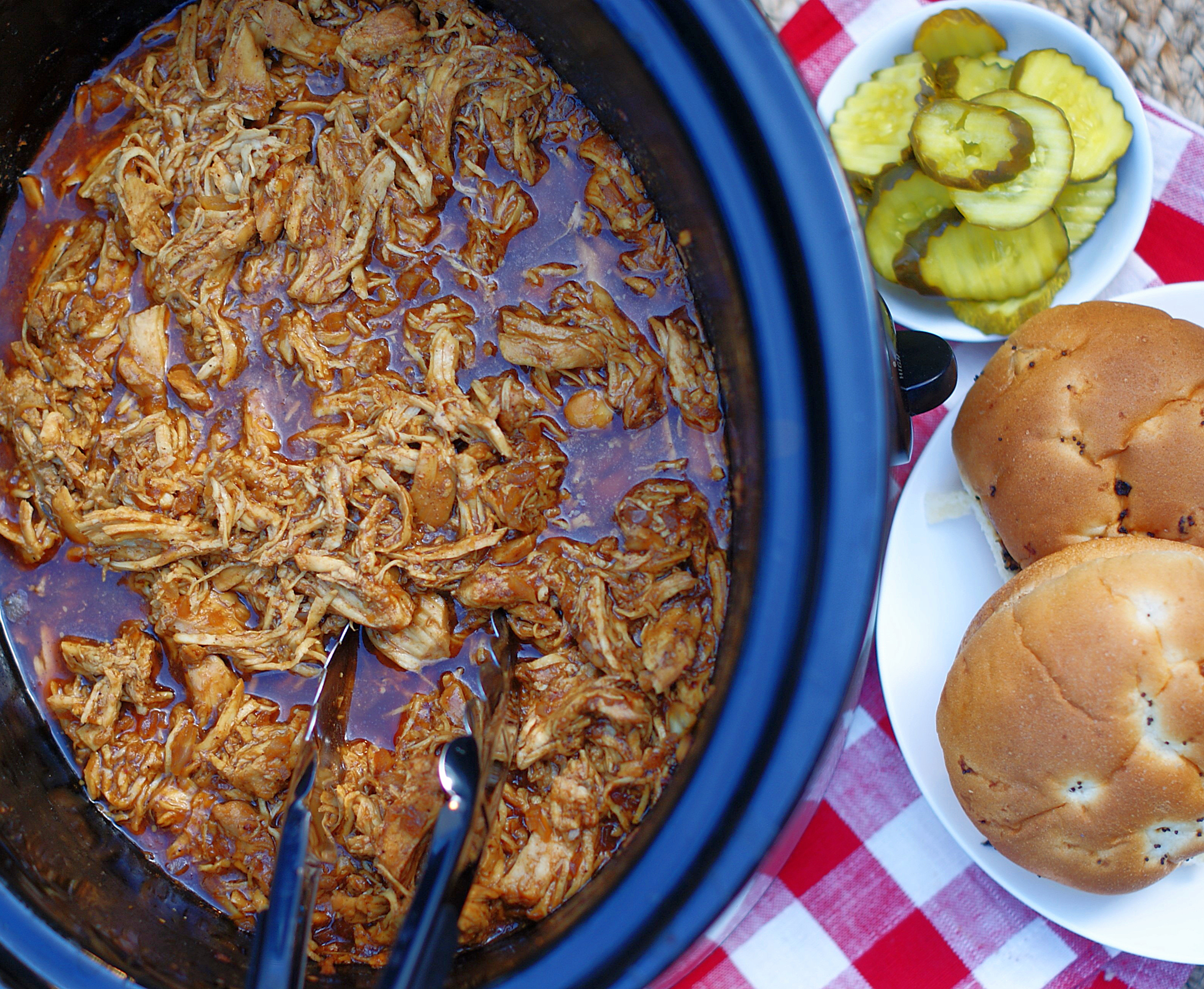 Finished BBQ shredded chicken in a crock pot with sandwich buns in the background.