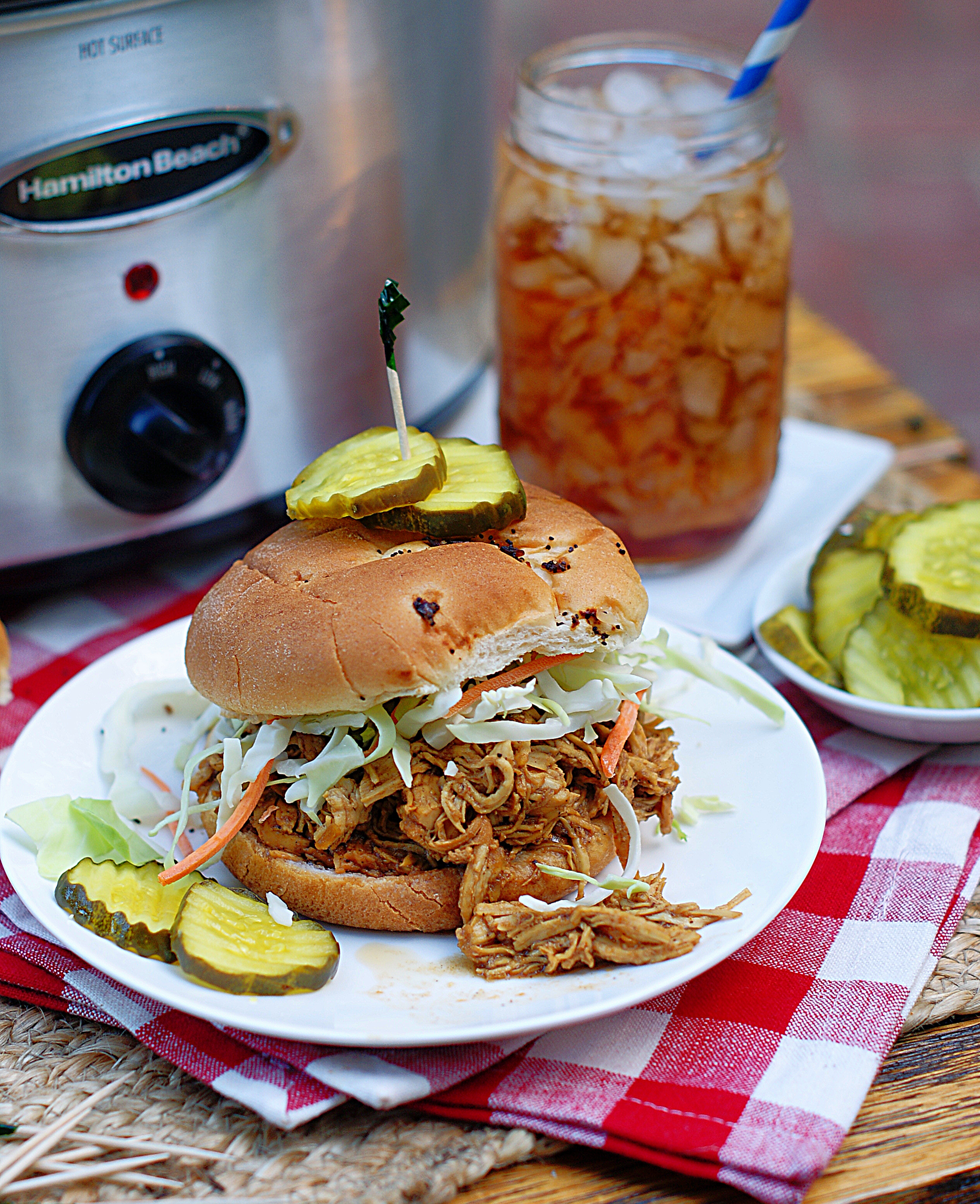 A Shredded Chicken BBQ Sandwich with pickles and a crock pot in the background.