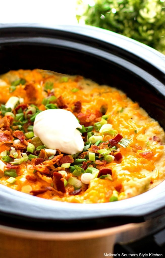Cheesy potatoes in a crock pot loaded with sour cream, green onions and bacon.