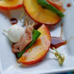 A summer appetizer treat of peaches, ham, mozzarella and basil