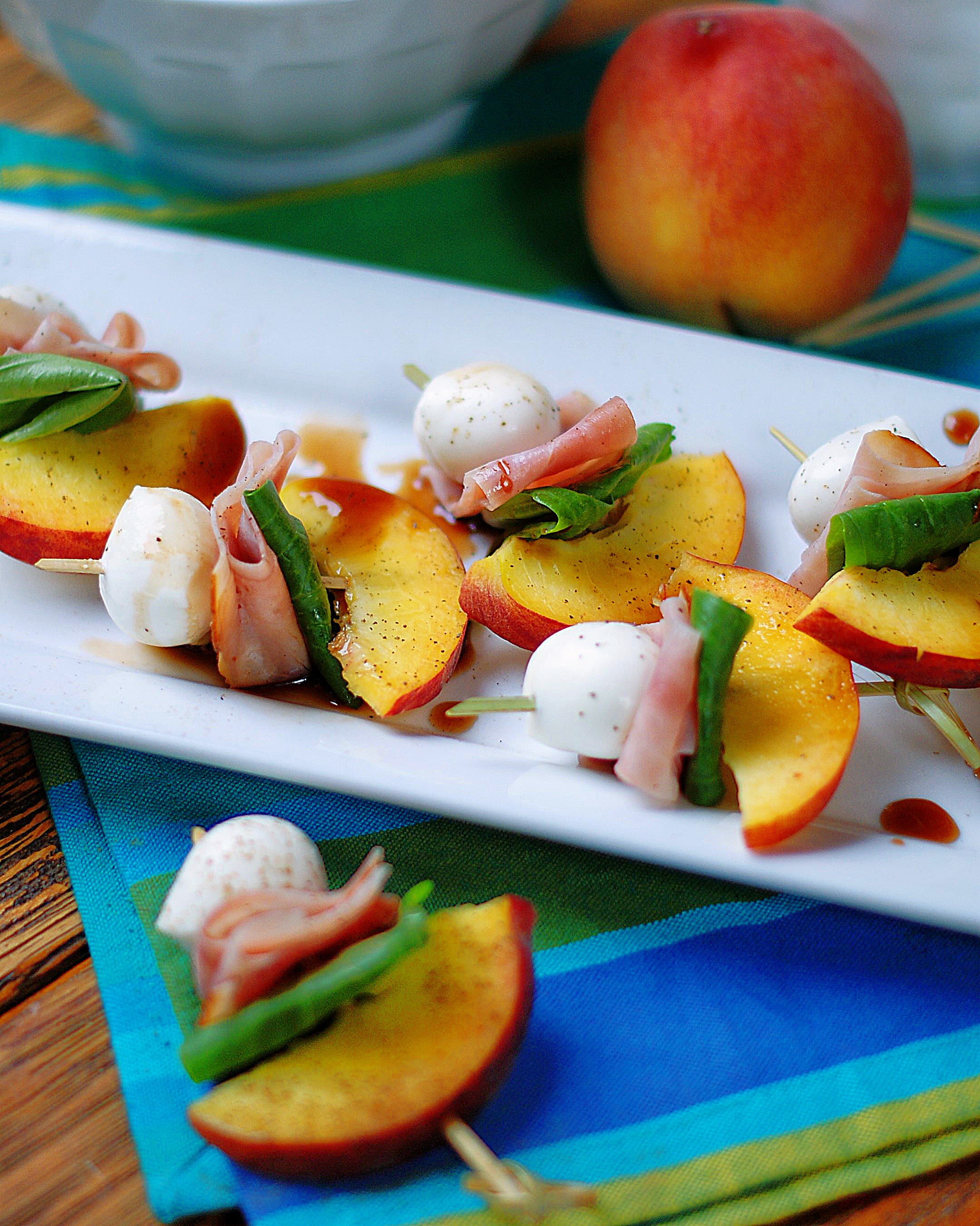 A tray of peach skewers with ham, mozarella, basin & a balsamic reduction.