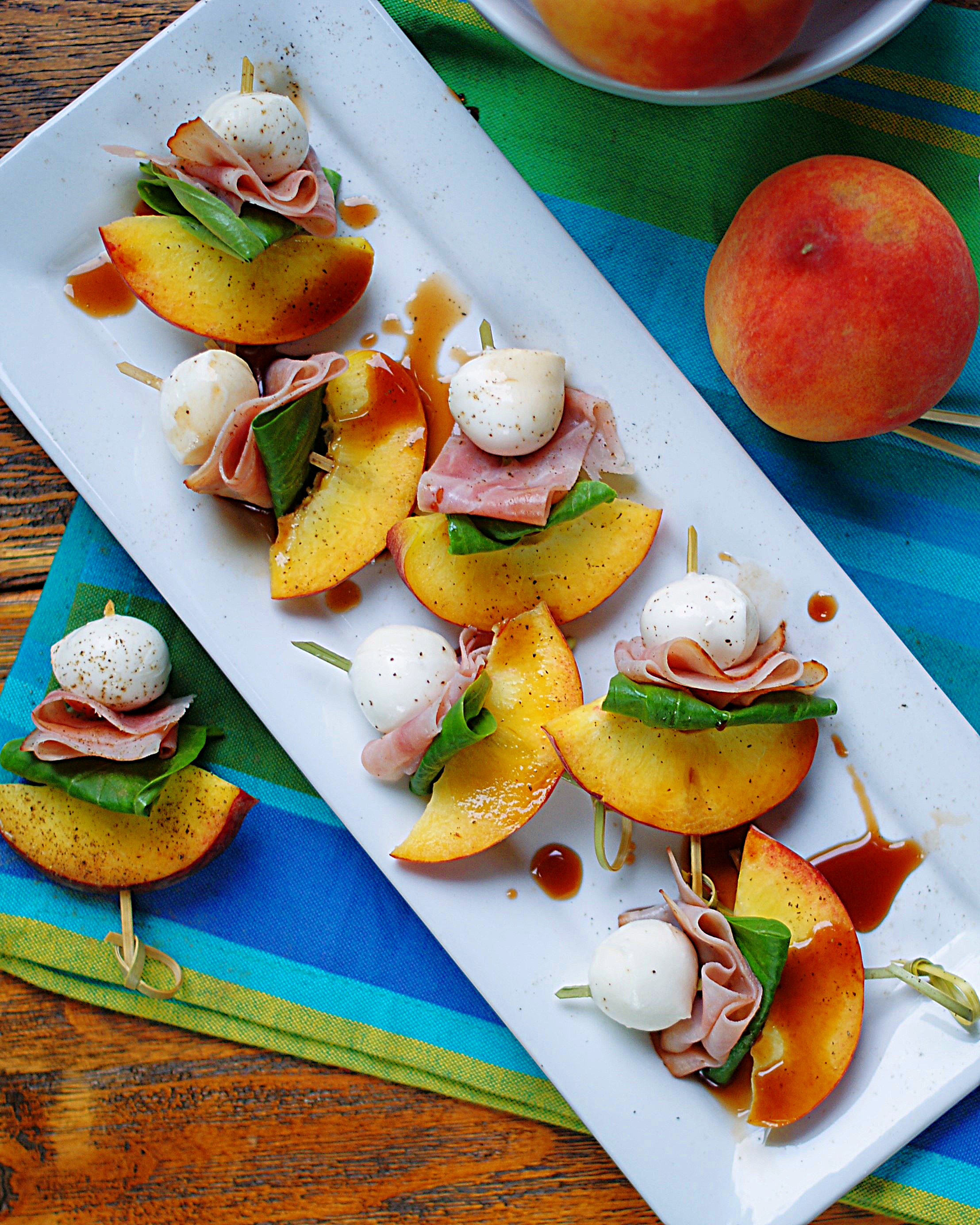 A party tray of peach skewer with mozarella, ham, basil and balsamic appetizers.