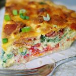 An upclose of a BLT Quiche slice, filled with tomatoes, bacon, spinach, green onions and cheese.