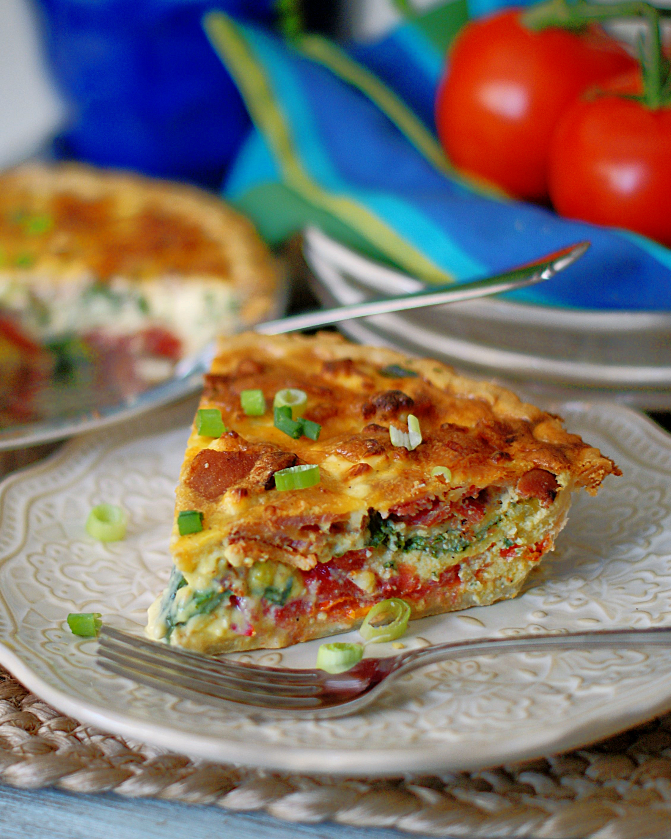 A slice of BLT Quiche with tomatoes in the background.