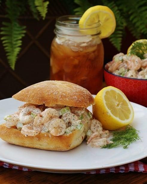 Shrimp Salad on a roll with a glass of iced tea.