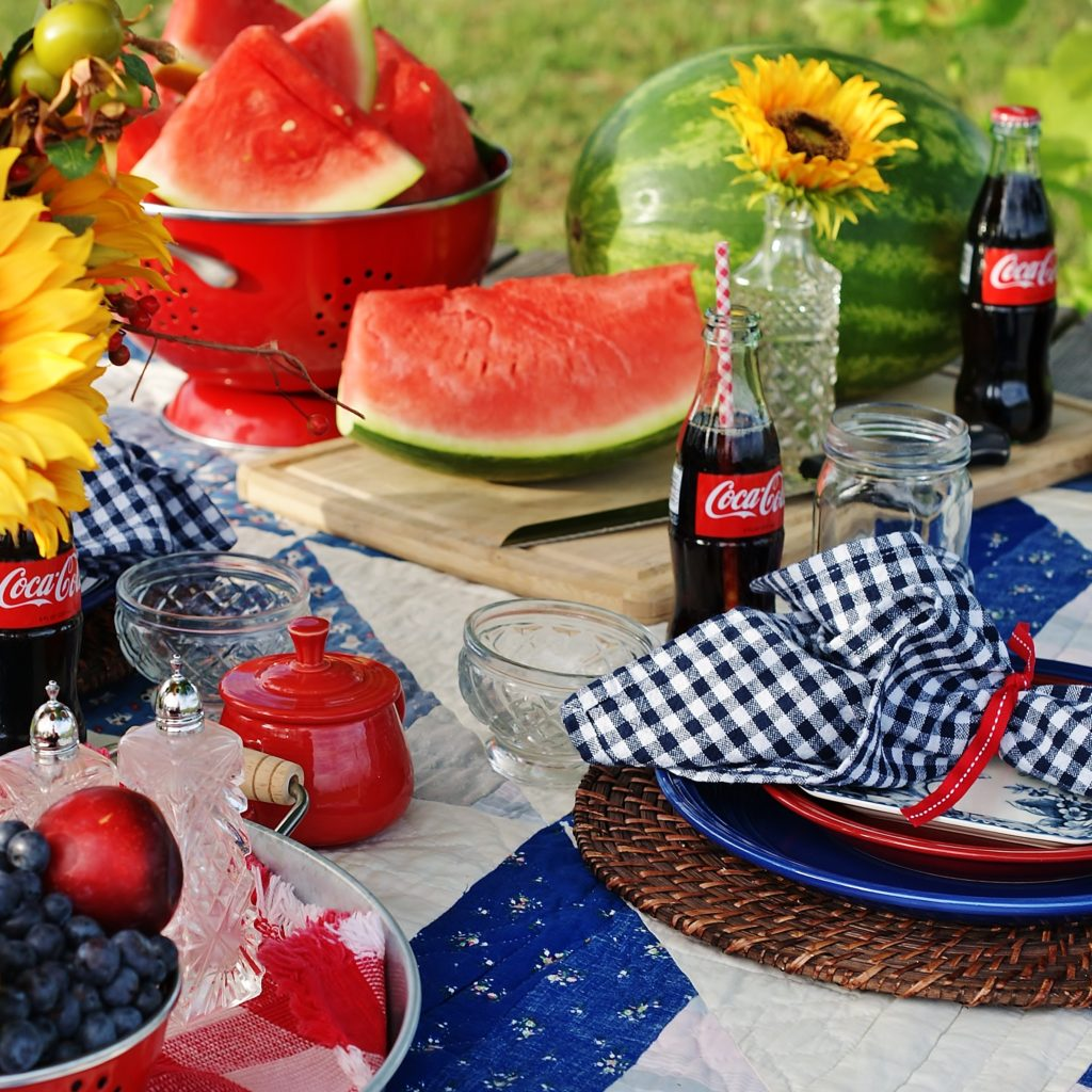 Watermelon and retro coca cola bottles dot this gingham and quilt spread july 4th picnic.
