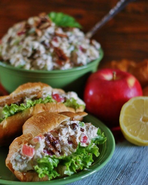 Tuna salad in a bowl and tuna salad on a croissant.