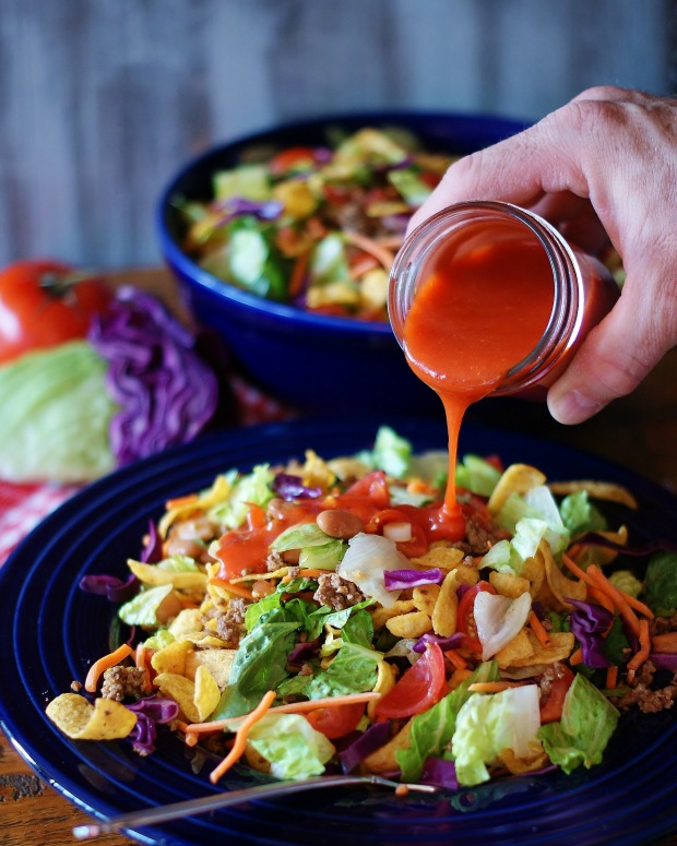 Catalina Dressing being poured over a taco salad with Fritos brand chips.