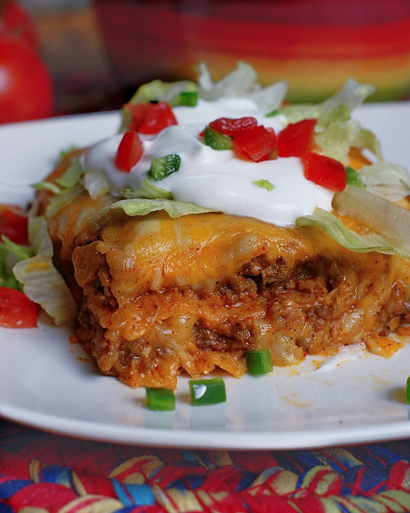 Layered Beef Enchiladas on a plate topped with sour cream, tomatoes & lettuce.