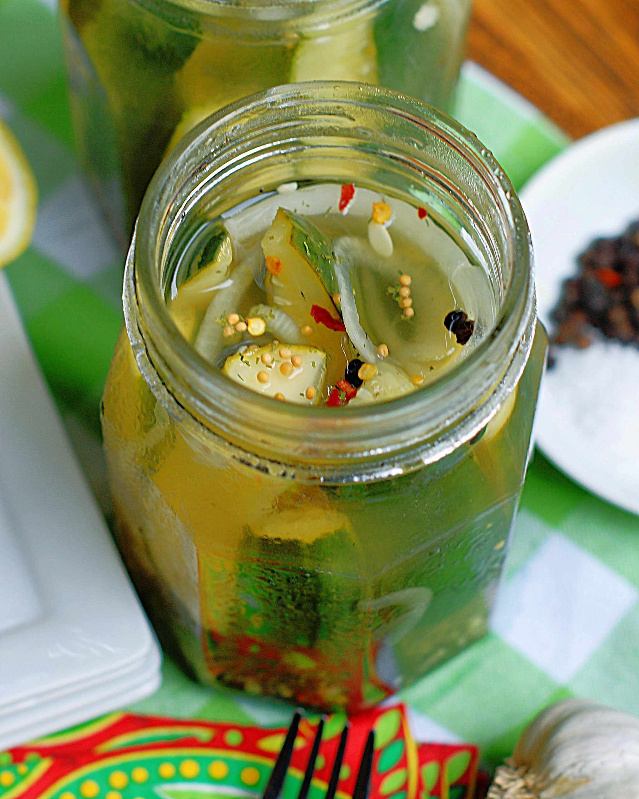 A jar of refrigerator pickles made with lemonade, garlic, pepper and dill.