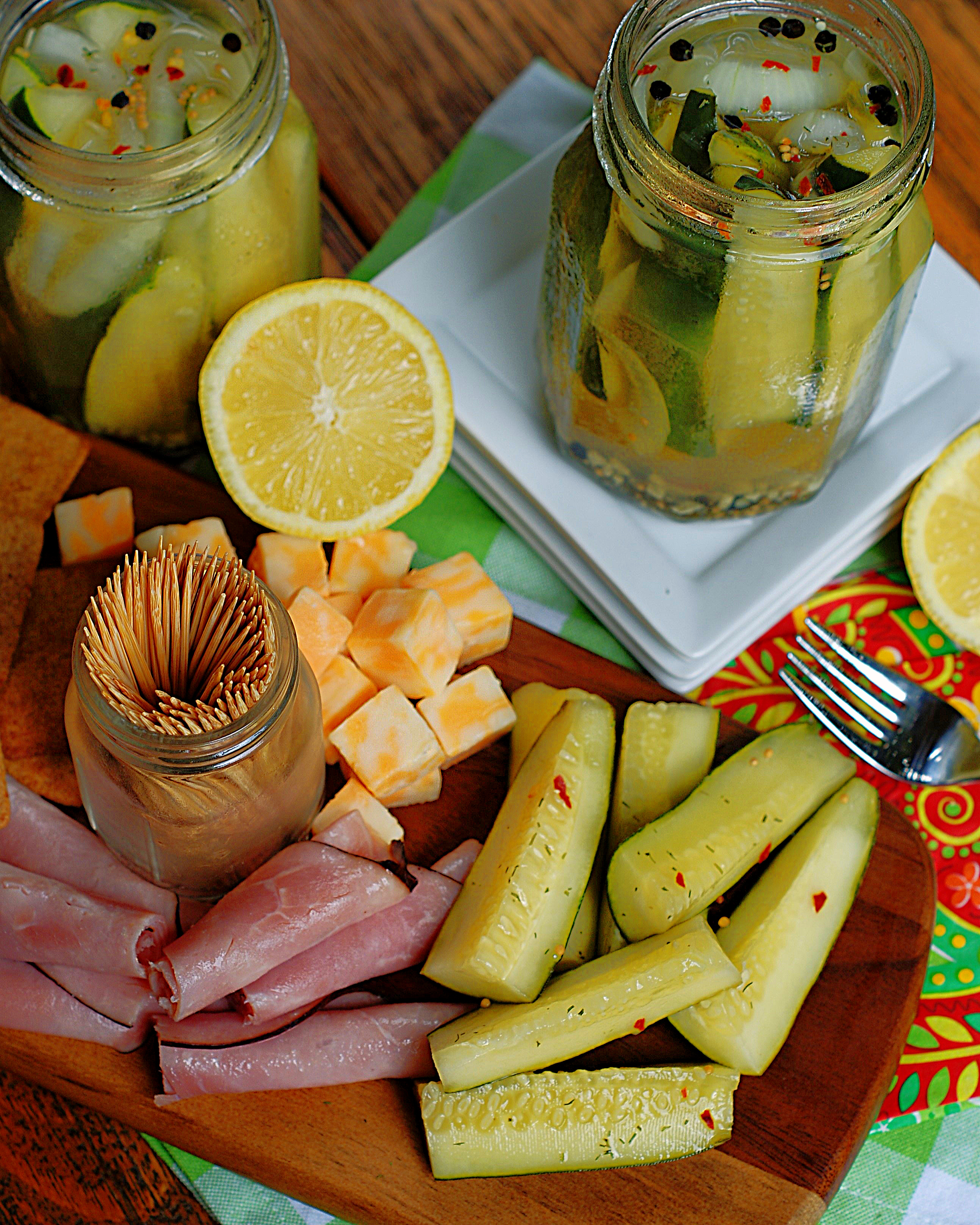 A cheese platter with lemonade refrigerator pickles.