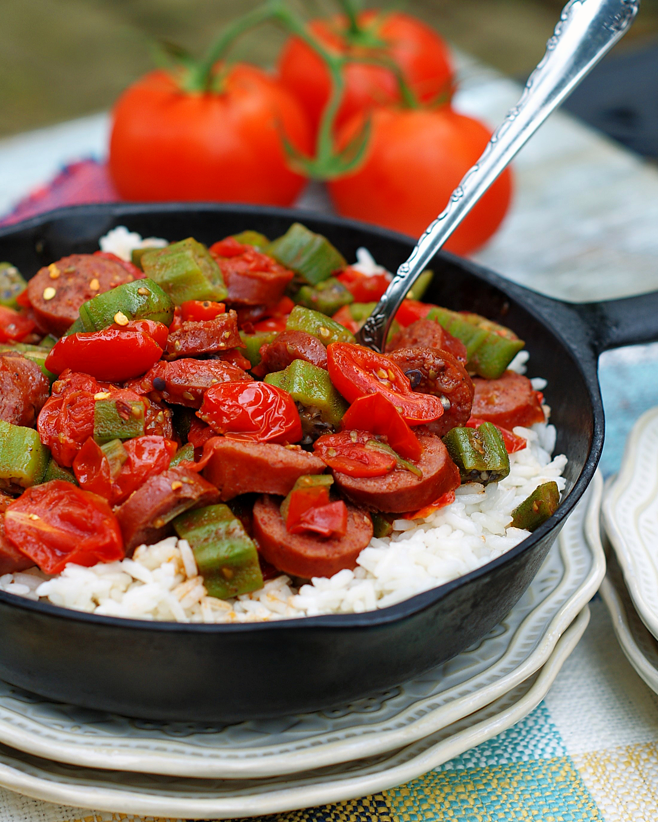 A skillet with white rice, sauteed tomatoes, okra and smoked sausage ready to be served.
