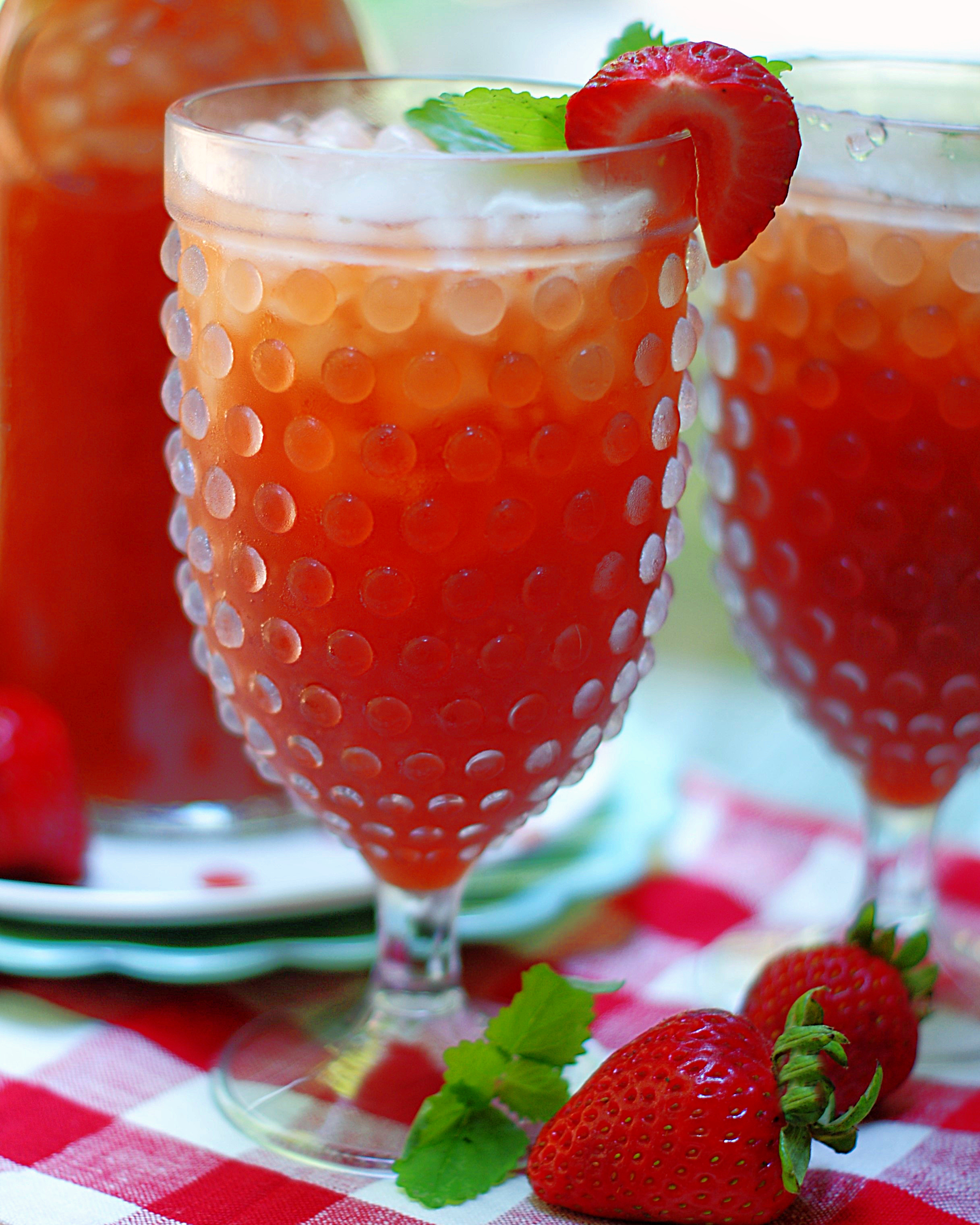 A stemmed hobnail glass with strawberry tea.