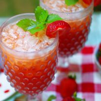 Two glasses of strawberry tea garnished with strawberries and mint.