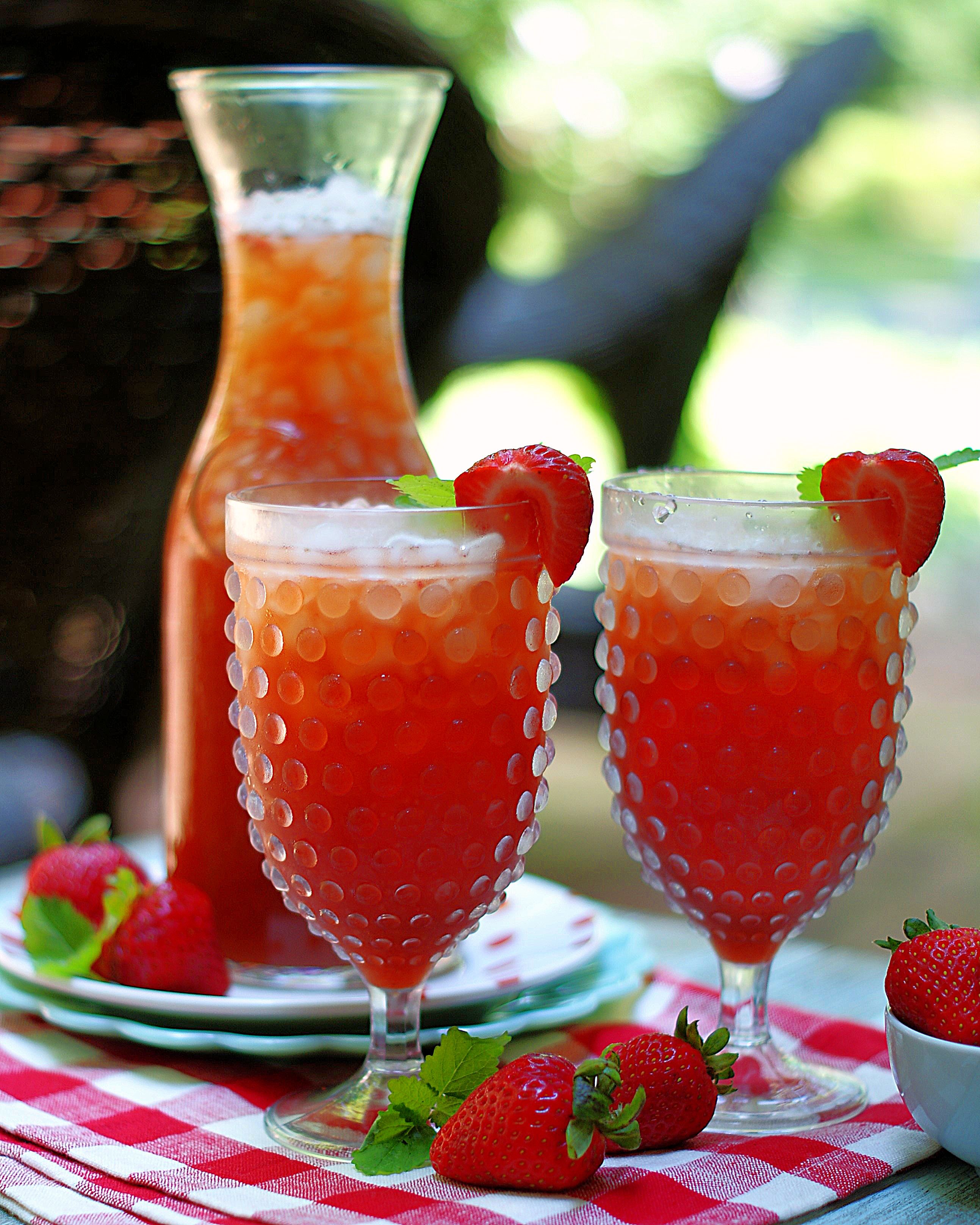 A carafe and 2 glasses of strawberry tea on the patio.