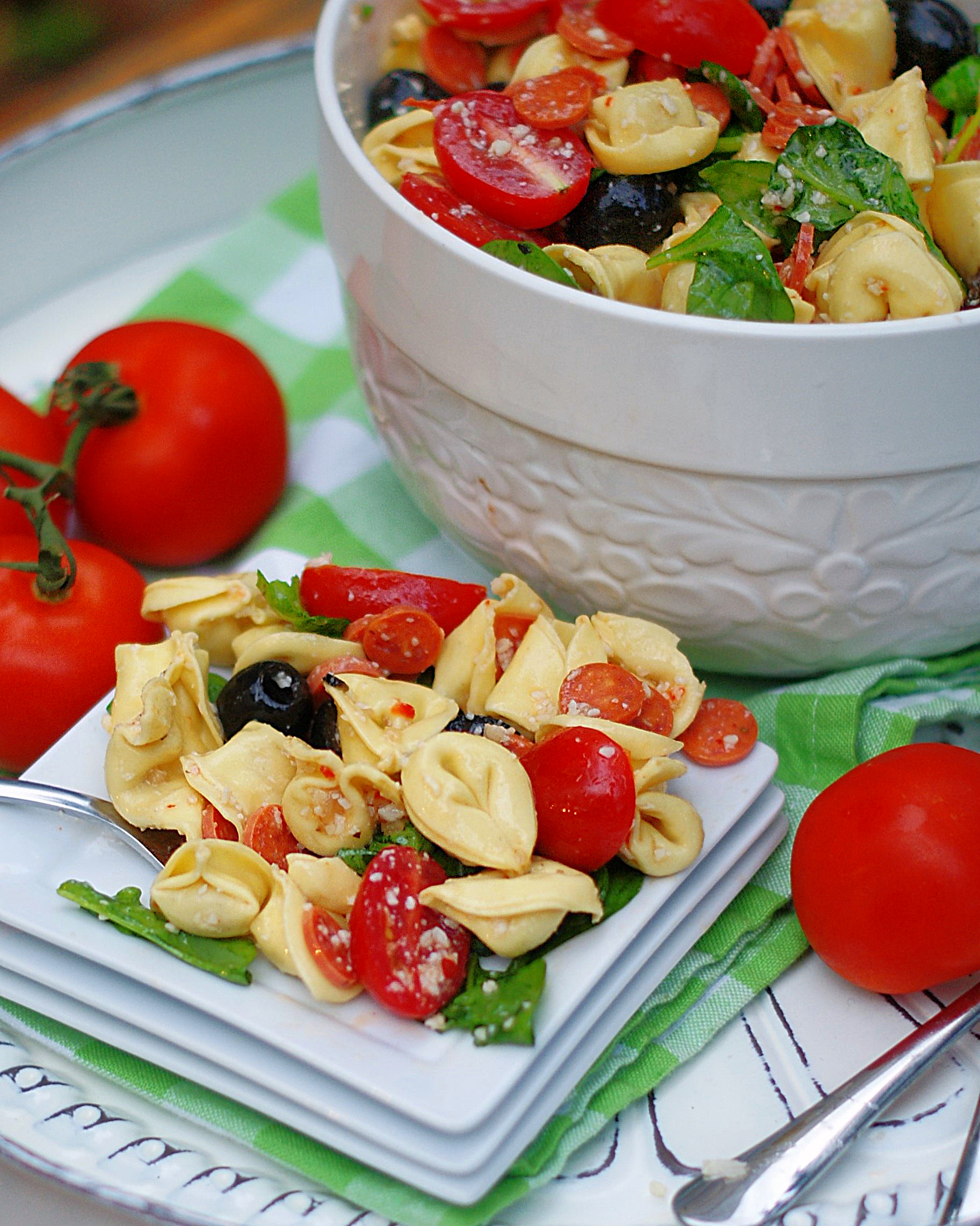 A serving of cold tortellini pasta salad on a plate.