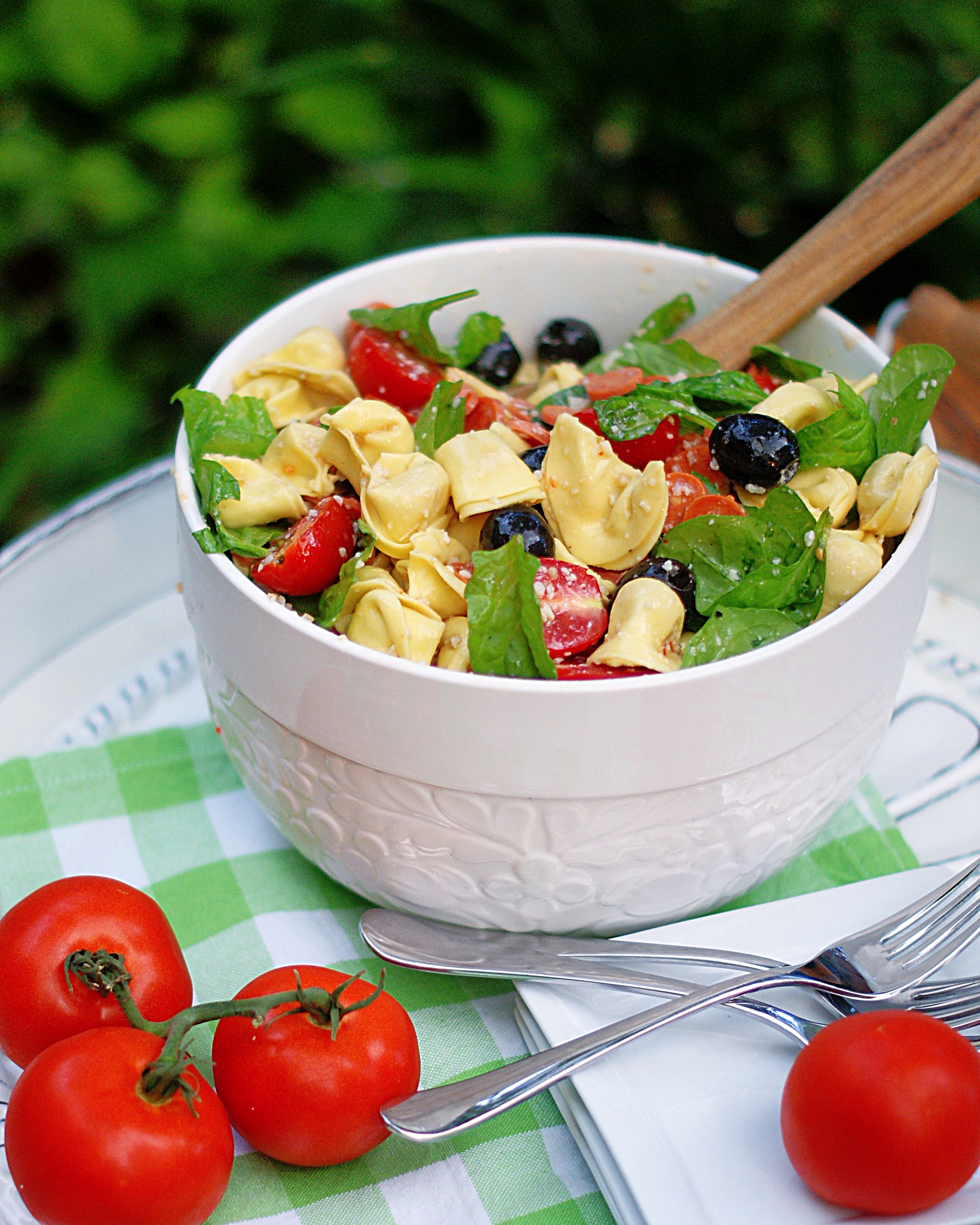 Tortellini Pasta Salad with olives, pepperoni, parmesan, tomatoes and spinach in a big white bowl.