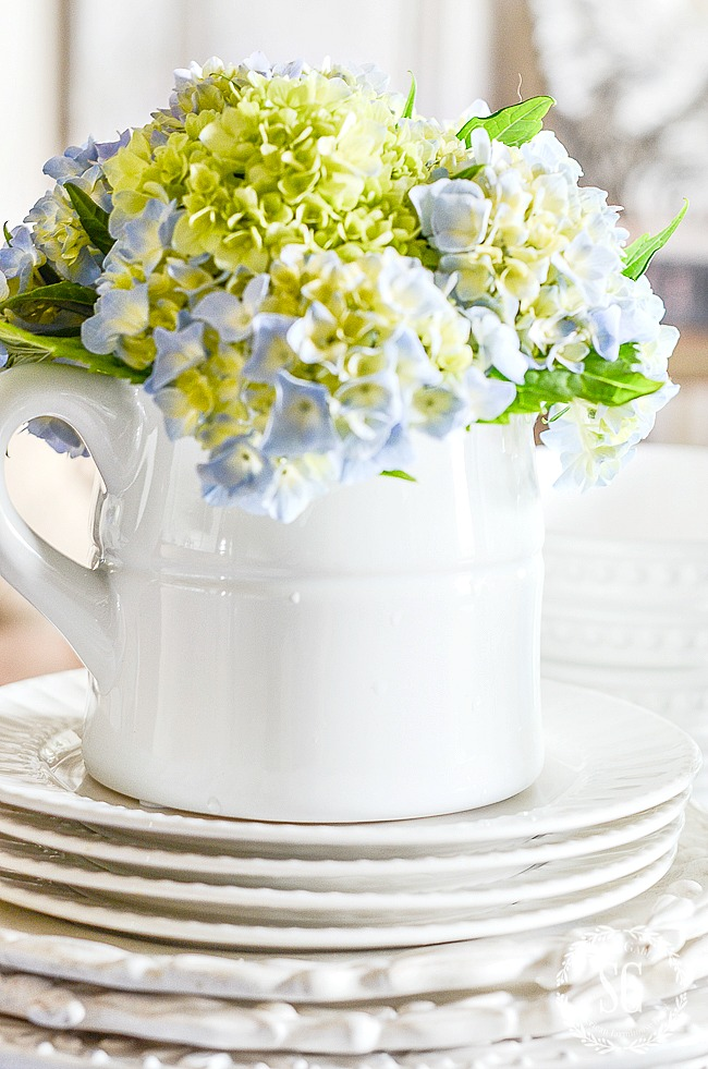 Hydrangeas in an ironstone pitcher with plates.