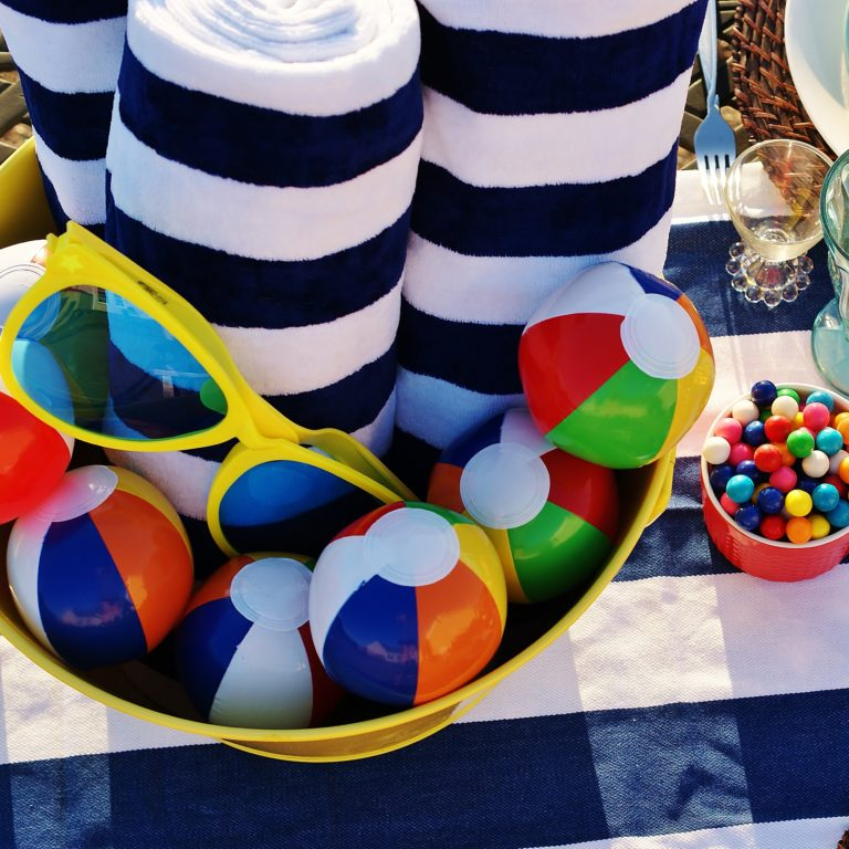 A bucket full of beach towels, balls and glasses for a Labor Day Pool Party.