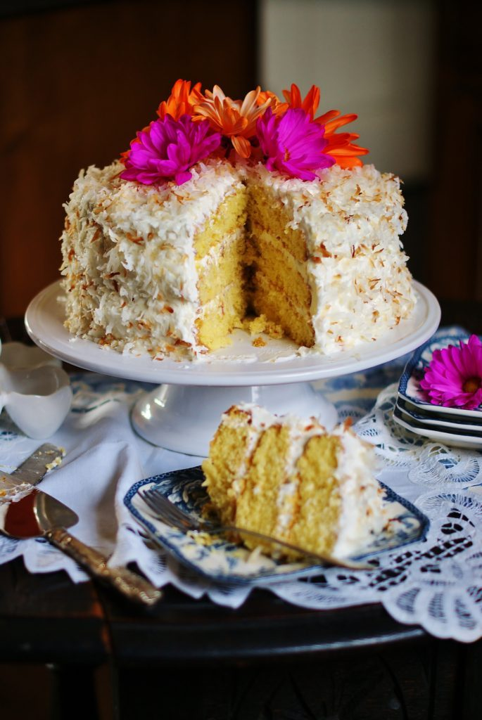 A sliced coconut ice box cake with sour cream frosting