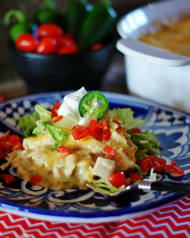 Green Chile Enchilada Casserole on a blue Mexican ware plate.