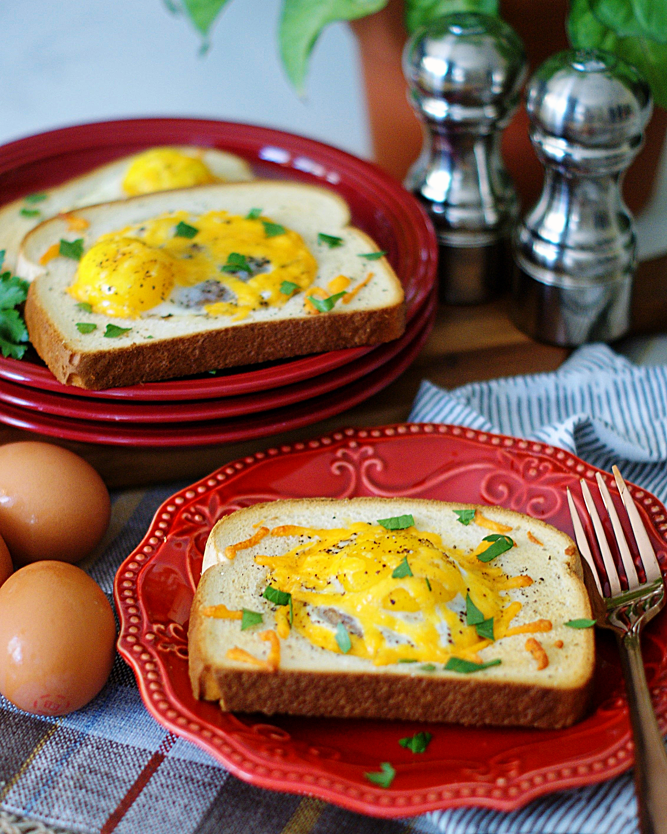 3 eggs in a basket on red plates ready for breakfast.