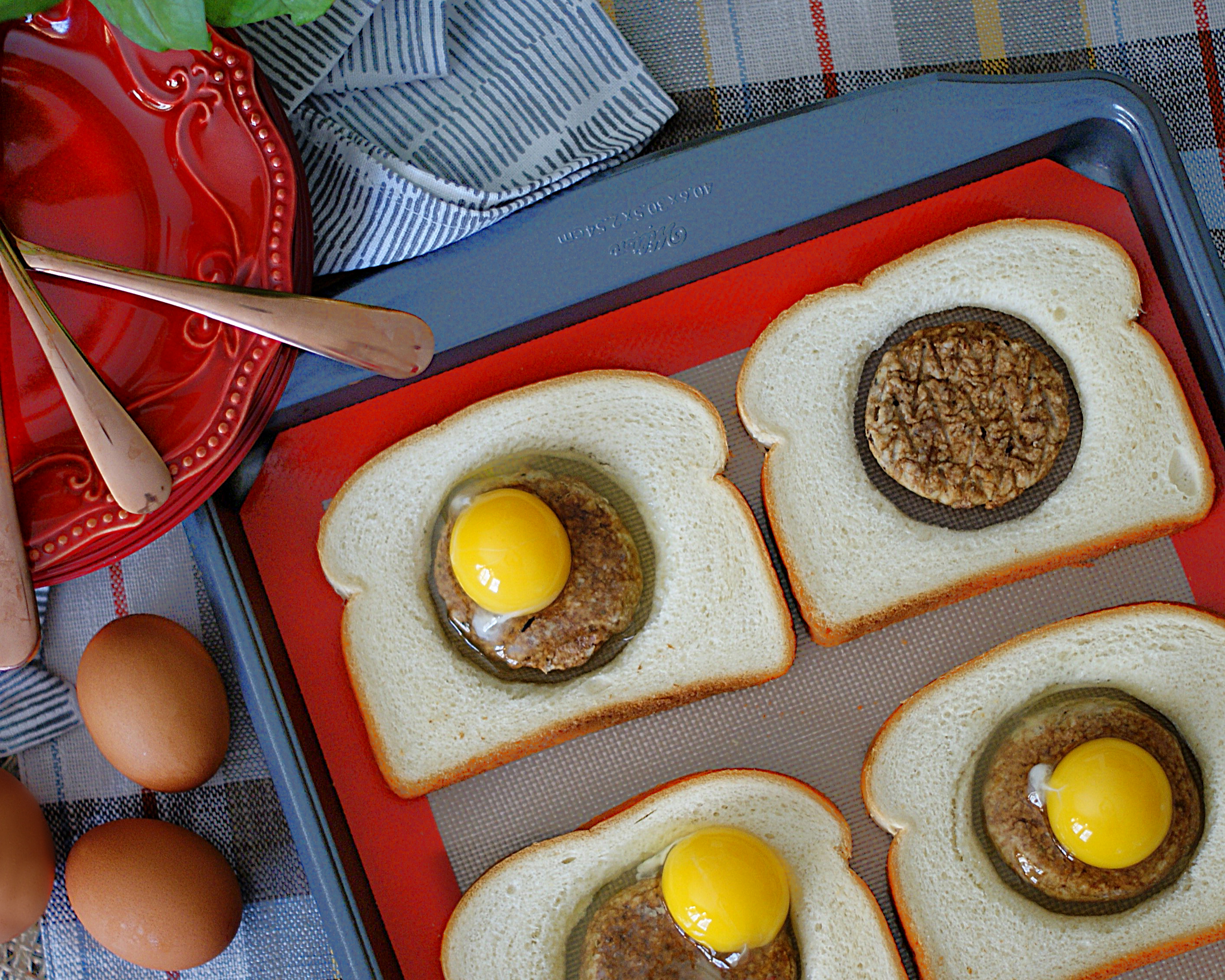 Sandwich bread with hole removed and filled with sausage and egg.
