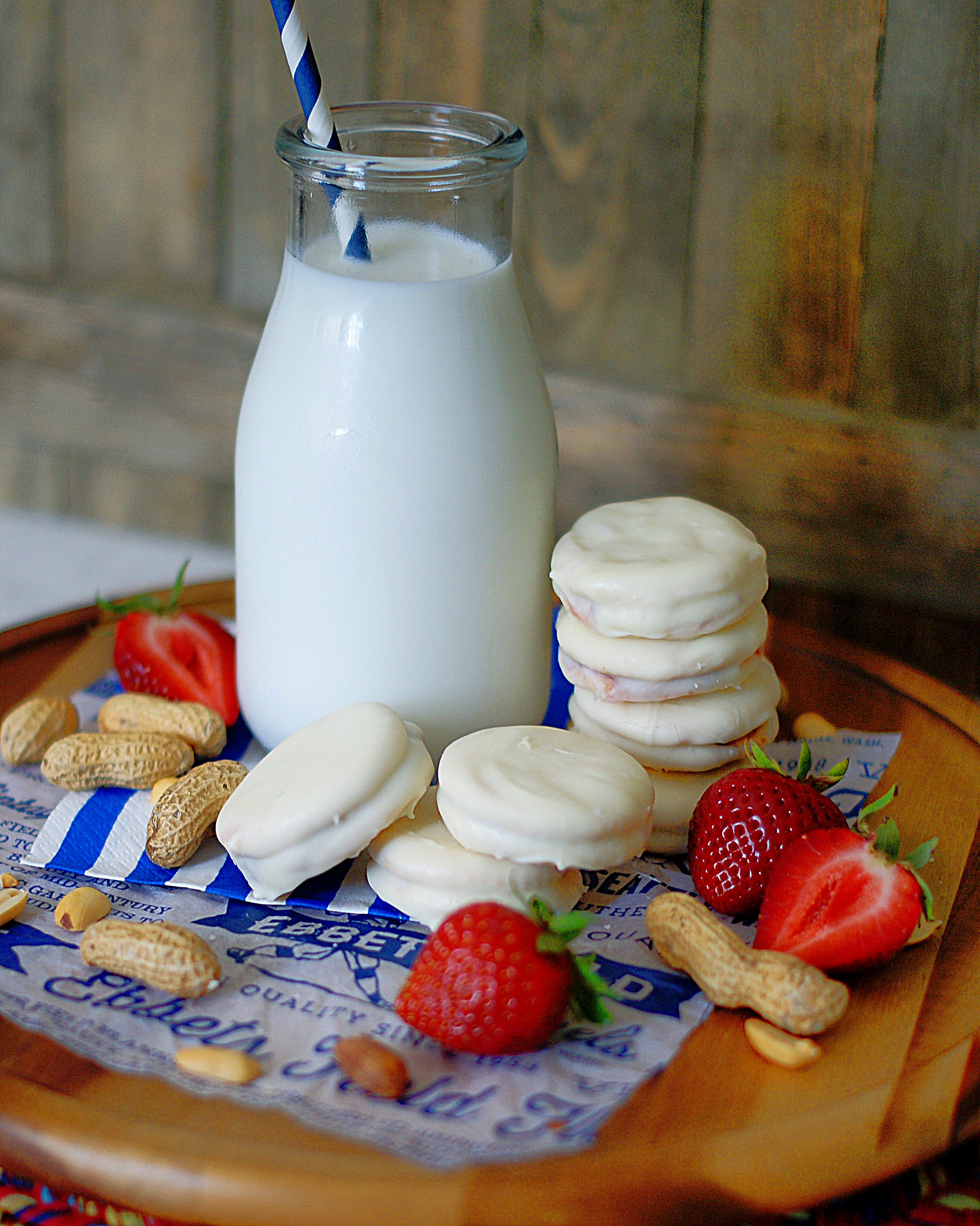 White chocolate dipped peanut butter & jelly crackers with milk and strawberries.